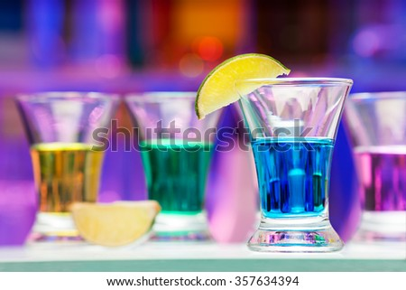 Several glasses with color drinks and lime in bar - stock photo