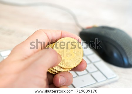 Several Golden Bitcoins In A Hand Near White Keyboard And Computer Mouse Electronic Money Mining