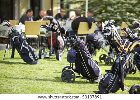 Several golf bags parking at club house with group of golfers sitting in background.
