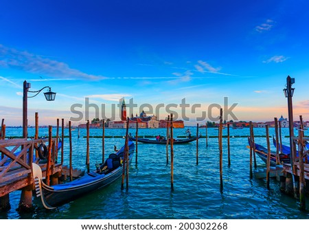 several Gondolas docked at Venice Italy. Sunset time