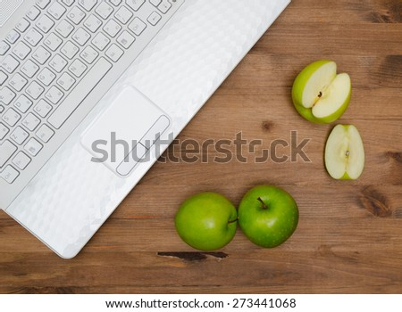 Several green apples and  laptop on old wooden table - stock photo