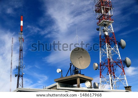 Several kind of communication antennas and a red and white tower - stock photo