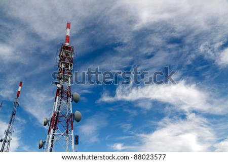 Several kind of communication antennas and red and white towers - stock photo