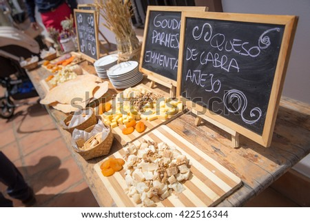 Several kinds of cheese served on vintage wooden table and blackboards written in spanish - stock photo