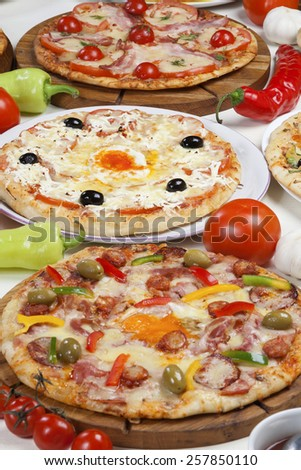 Several kinds of pizza served on the table. - stock photo