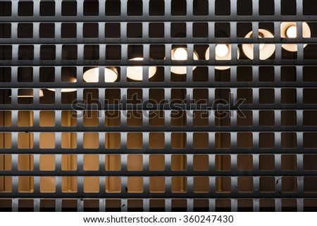 Several lamps lit behind a bars in different positions