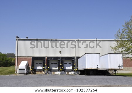several large trucks parked by unloading docks