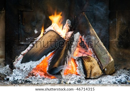 Several logs burning in a small fireplace surrounded by ashes, smoke and flames - stock photo
