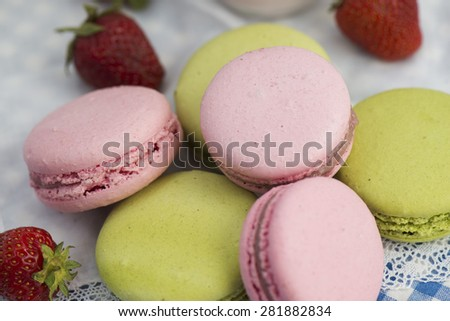 several macaroons and strawberries on the table