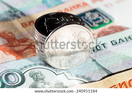 Several metal coins of one ruble standing on Russian paper banknotes - stock photo