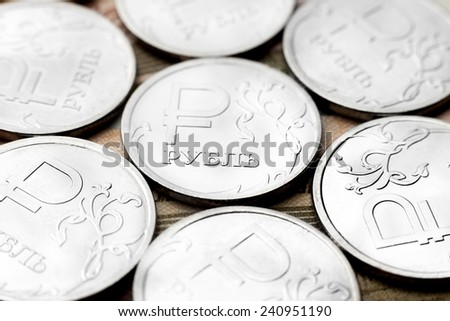 Several metal coins of value of one ruble that lie on Russian paper money - stock photo