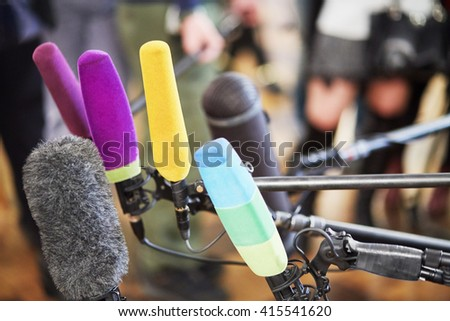 Several microphones prepared for press conference.