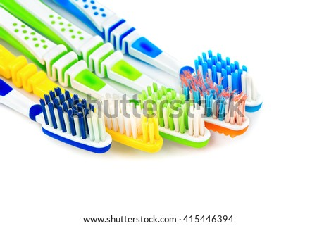 Several multi-colored toothbrushes on a white background closeup - stock photo