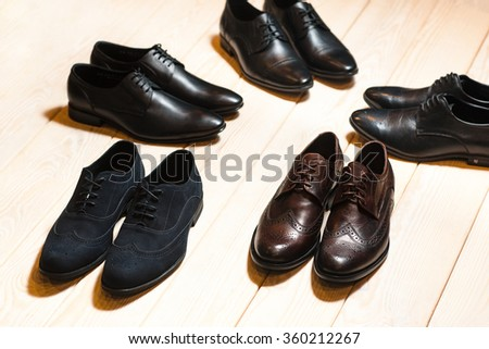 Several new pair of leather shoes for men on a wooden background with lots of free space.The concept of business meeting