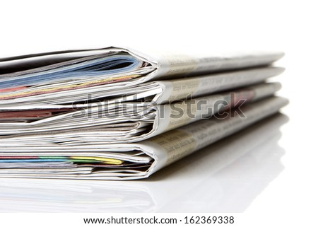 several newspapers, journals stacked on white background
