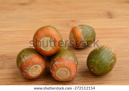 Several oak acorns on wooden background, close up view - stock photo