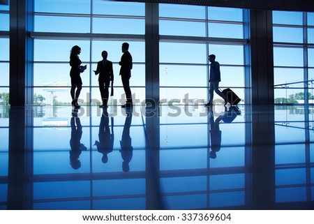 Several office workers talking by the window inside modern office building