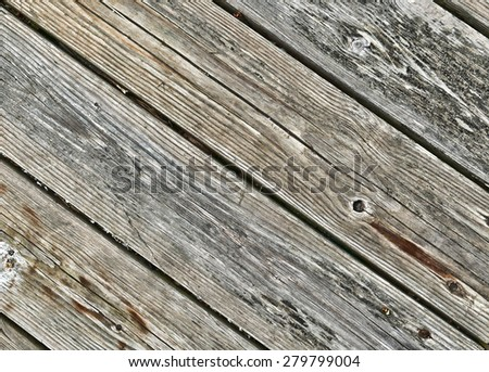 Several old decking boards which are rotting at an angle. - stock photo