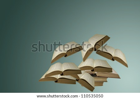 Several open books floating in the air - stock photo