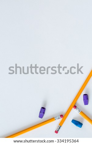 Several pencils and erasers placed in a pleasing way on white paper to create a border for multiple purposes. This can be used as a vertical or horizontal format or it can even be flipped and rotated. - stock photo