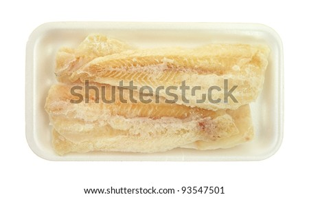 Several pieces of frozen pollock on a white foam tray. - stock photo