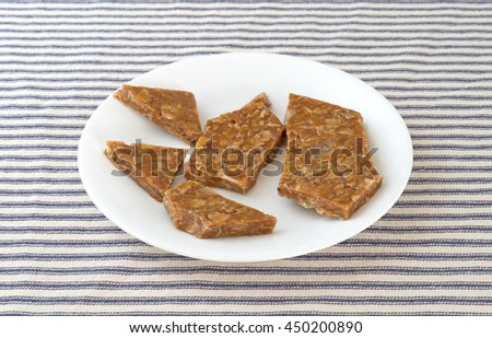 Several pieces of ginger brittle on a white plate atop a blue striped tablecloth.