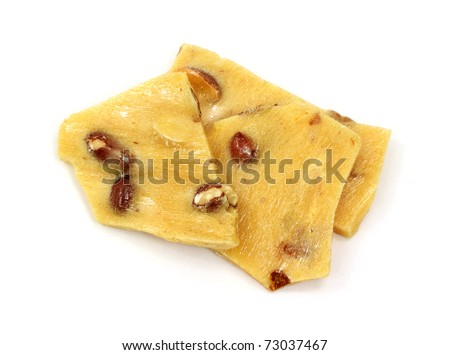 Several pieces of peanut brittle on a white background. - stock photo