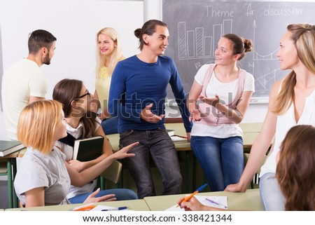 Several positive students having a conversation sitting in the classroom - stock photo