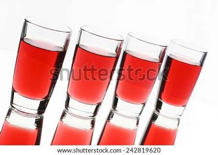 Several red alcohol shots on white background - stock photo