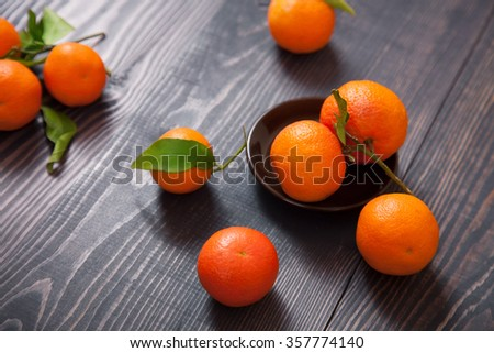 Several ripe tangerines on a dark wooden table - stock photo