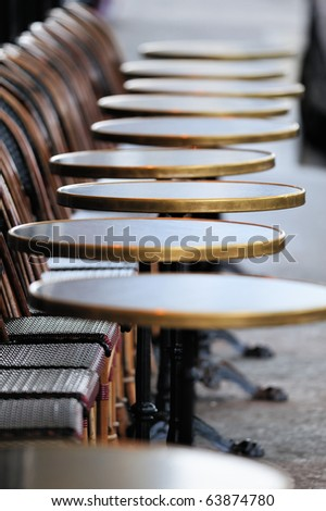 Several round tables in the  typical cafe in Paris. Photo with tilt-shift effect - stock photo