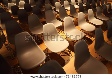 several rows of white plastic chairs with metal legs on yellow floor - stock photo