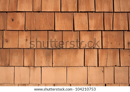 Several rows of worn rustic painted shingles.