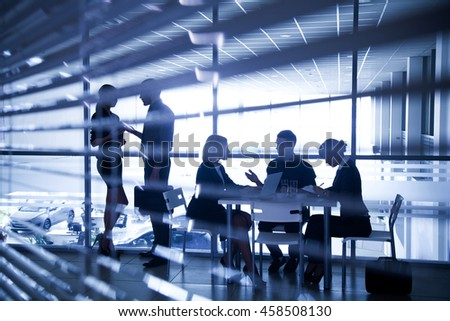 Several silhouettes of business people interacting  background business center - stock photo