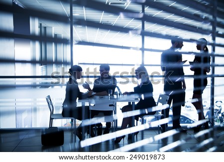 Several silhouettes of businesspeople interacting  in office