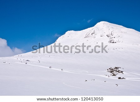 Several skiers climbing uphill with a mountain summit on their right hand in the norwegian mountains at easter