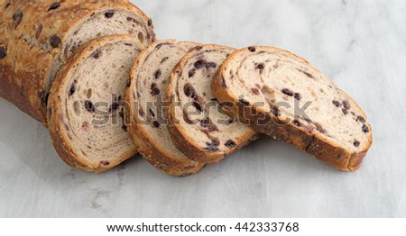 Several slices of blueberry streusel bread from a loaf on a marble cutting board. - stock photo