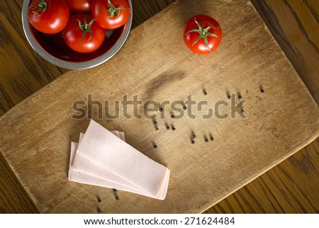 Several slices of Romanian baloney on a wooden table with cherry tomatoes in metallic bowl. Top view - stock photo