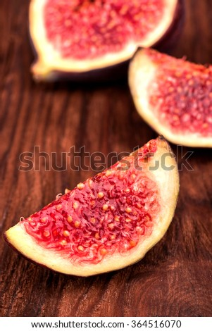 Several slices of sliced fresh figs on a wooden background