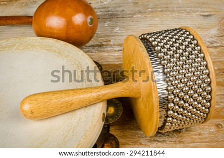 Several small percussion instruments on a rustic wooden surface - stock photo