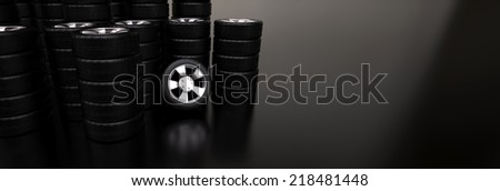Several stacks of car tires on reflective floor - stock photo