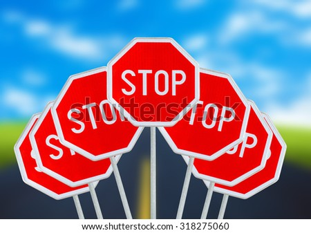 Several STOP sign on blurred road - stock photo