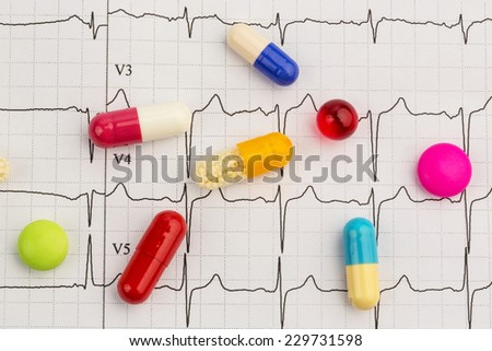 several tablets are on an ekg. photo icon for diseases of the heart and circulation - stock photo