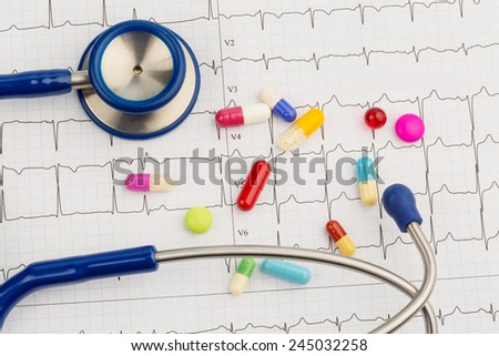 several tablets lie on an ekg. symbolic photo for diseases of the heart and circulation - stock photo