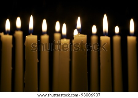 Several tall candles lit in a dark room. - stock photo