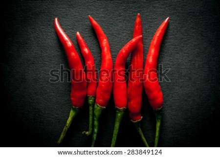 several Thai hot red chili pepper on a black background. Contents of capsaicin pepper determines the sharpness - stock photo