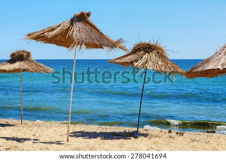 Several thatched beach umbrellas against the backdrop of a calm blue sea on a clear sunny day. Straw parasols. Selective focus on the umbrellas. - stock photo