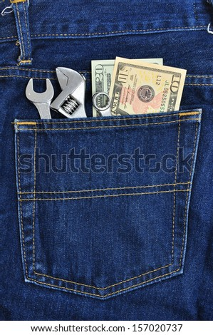 Several tools and dollar banknote in pocket