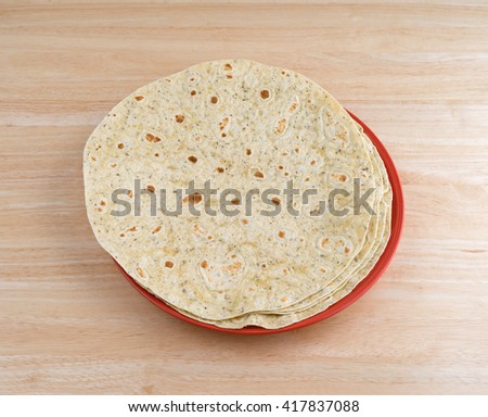 Several tortilla wraps with garlic and herb flavoring on a colorful plate atop a wood table top. - stock photo