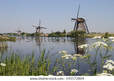Several traditional Dutch windmills alongside a canal near Kinderdijk, The Netherlands - stock photo